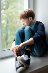 SadSad teen sitting on window